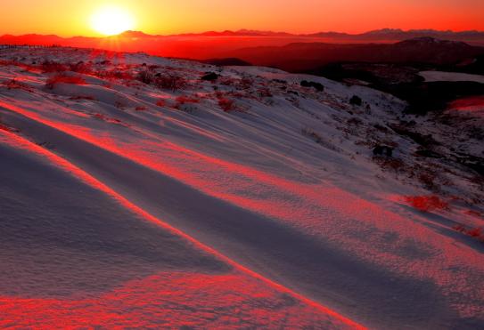 御岳に沈む夕日に映えるシュカブラと北アルプス