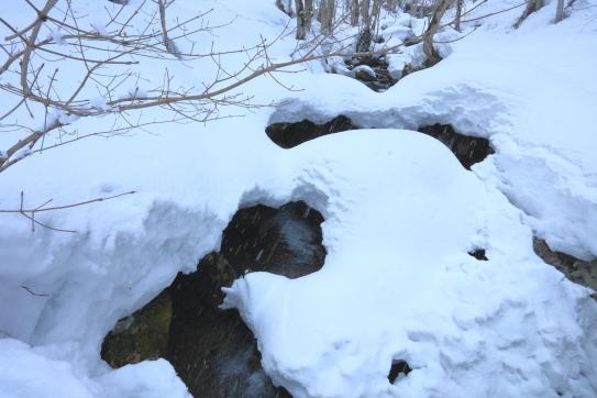 深い雪に閉ざされている宇津江川の降雪