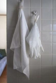 キッチンの壁に白いタオルと炊事用手袋