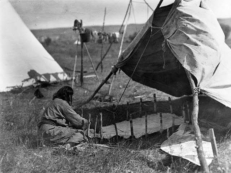 Native American woman creating a parfleche