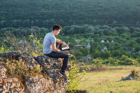 44434604-崖の端に座って、本を読んで男
